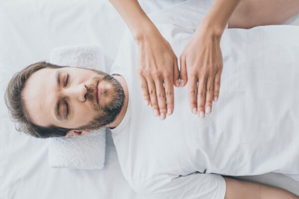 top view of bearded man with closed eyes receiving reiki treatment